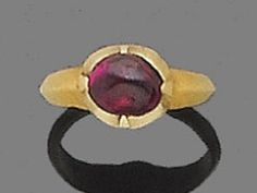 A 16th century ruby and gold child's ring  The cabochon ruby within a pinched collet setting