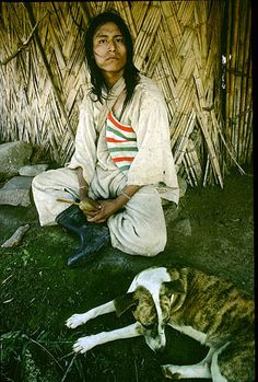 Colombia. Sierra Nevada de Santa Marta. Kogi Indian sits outside his straw hut. He is holding a gourd with a stick in it. He uses the stick to grind coca leaves, a mild narcotic,  and mix them with lime. One of his cheeks is inflated by a ball of that combination.