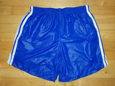 Shiny royal blue shorts athletic fit, medium length, with stripes and side slits. Thin material but very nice.