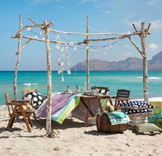 Udendørs stole og et bord på stranden med en farvestrålende dug med batikmønster og farvestrålende puder.