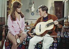 """""""20世紀最高のグラマー""""と称された肉感的なボディを、ピンクのガウンから大胆にのぞかせたラクエル・ウェルチ。こちらは、スペインを舞台に全米スカイダイビングチームのエースとしてウェルチが活躍する映画『空から赤いバラ』(1967年公開)でのひとコマ。大胆なカットのローブにビッグなヘアブラシなど、往年のアメリカンなスタイリングに注目を。"""