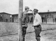 A French prisoner tied to a stake at Zwickau prison camp is given a drink by a fellow POW during the Great War.