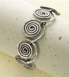 Textured spiral links with a matching clasp. From Step by Step Wire Jewelry, April/May 2010.#wire #jewelry #spirals
