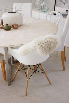 Sillón Eames con mantita de corderito en una mesa de marmol