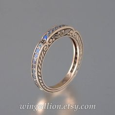 This breathtaking wedding band was designed by the artist and jewelry designer Sergey Zhiboedov. It will be made to order in 14k rose gold in the size specified by the customer.  The gold band is designed to be worn with one of our most popular ring designs - the Caryatid ring. Still, it can stand on its own as a refreshing alternative to an eternity band.  The CARYATID bands sides are adorned with scroll carvings. On the top, there are 28 genuine 1.5mm rainbow moonstones. The stones are…