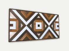 MADE TO ORDER This amazing geometric wood wall art is made from reclaimed wood. This has a modern, yet rustic appearance and would look wonderful in any decor. Size is 50 1/2 X 24 1/2 X 2 Weight is 24lbs Looks great hanging vertically or horizontally. Stained in earthy tones of walnut and pecan as well as white and tan acrylic paints. Finished with 2 coats of water based sealer to protect the beauty of the wood. Comes with attached heavy duty D rings and picture wire.