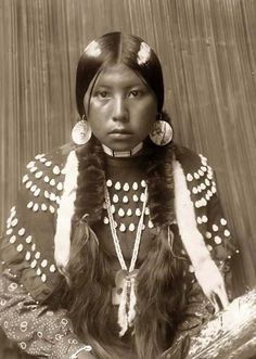 "A beautiful photograph of an indian maiden named ""Dusty Dress.""  It was taken in 1910 by Edward S. Curtis & is of a Kalispel Indian girl in a half-length portrait, facing front, seated, wrapped braids, white stripes painted on hair, shell disk earrings, wearing blanket dress decorated with elks' teeth."
