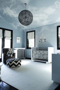 The whisper soft cloud mural on the ceiling takes my breath away in this modern, yet cozy, gender-neutral nursery