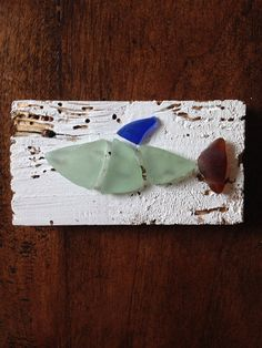 Fish made of sea blue, cobalt, and brown sea glass, adhered to recycled wood panel. Sea glass is genuine surf tumbled and collected from the San