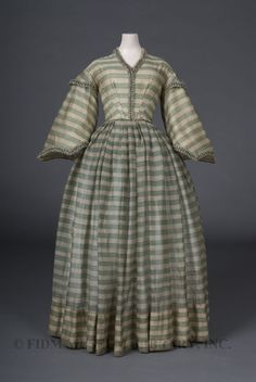 CRINOLINE DAYTIME DRESS (1858)- the simple and muted pattern would most likely be worn during the day time, once again the skirts shape indicates a crinoline. (Crinoline Period)