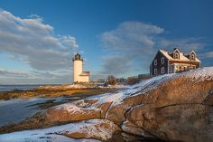 Beautiful Annisquam Lighthouse on the North Shore of Massachusetts, near Gloucester, bathed in early morning light with a light dusting of snow on the granite boulders in the foreground.