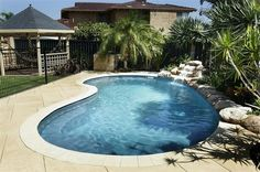 spectacular kidney shaped swimming pools design waterfall feature exotic palm trees