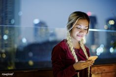Smiling young woman using a smartphone in the evening cityscape   premium image by rawpixel.com