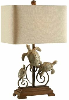 Create a captivating beach cottage style with this 26inch tall resin table lamp with afamily of turtles perched on a decorative metal swirl. A natural linen rectangle shade completes the look. Perf