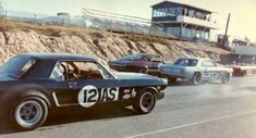Mustangs competing in an old Trans Am style race.