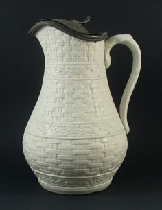 An English 19th century stoneware jug or pitcher by Thomas Booth Sons decorated with a relief moulded basketweave design and mounted with a hinged
