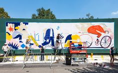"""A slew of local artists put up murals on the 16-foot-tall green construction fence — recently dubbed the ""Green Monster"" — along Dean Street in Prospect Heights during Saturday's 10 Murals/1 Day block party thrown by Atlantic Yards/Pacific Park developer Greenland Forest City Partners."""