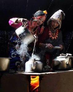 Women prepare to serve tea in Tibet.