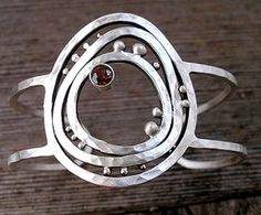 Cuff | Delias Studio Designs. 'Puzzled Pebble'. Sterling silver and garnet.