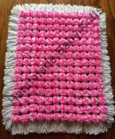 Multicolour pink pom pom blanket with white base and tassles.