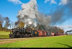 Colorful Cherry Hill. A westbound, steam-powered mixed freight passes and eastbound passenger train at Groff's Grove, near the tiny Cherry Hill Station in Ronks, PA.