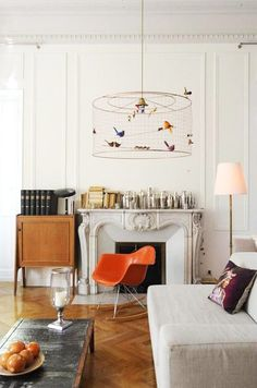 retro orange fiberglass eames chair via sfgirlbybay | white ornate fireplace | white panelled walls and wooden herringbone floors | linen boxy sofa | Get the look with an IKEA Kivik sofa and a Bemz cover in Unbleached Linen