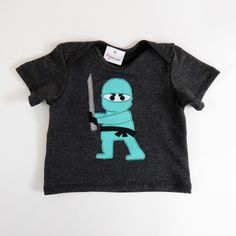 Glammic Charcoal Baby Tee with Ninja Applique. The perfect baby tee for your little ninja! In charcoal, with a hand cut & sewn Ninja applique. $35.  Limited Edition.