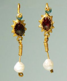Roman Gold, Glass and Pearl Earrings A pair of ancient Roman granulated gold earrings inlaid with garnet and set with a glass bead at the top and antique pearl drops. Ca. 1st - 3rd century AD.