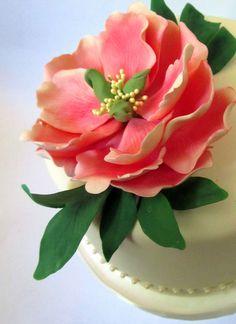 Handmade gumpaste peony adorning a pearl-trimmed wedding cake.