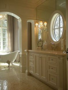 Such a beautiful bathroom, great architectural details in the mouldings, arched opening, round window and those sconces!