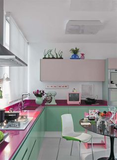 Colorful mint green kitchen cabinet and orchid purple countertops