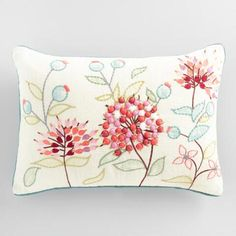 Dreamy pink and red poms portray the petals of agapanthus flowers blooming across the natural backdrop of our lumbar pillow with teal piping.