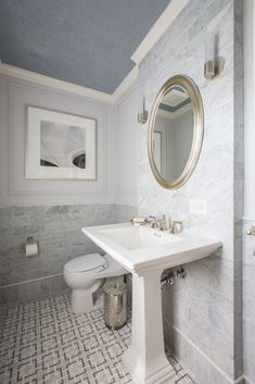 Powder room walls are enhanced with panel moulding and Carrera marble tile; luxury mosaic of Turkish gray, Thassos, and Carrera marbles provides visual interest for the floor; glass-beaded ceiling wall covering was fabricated by Maya Romanoff; powder room was created by remodeling a former full bath and relocating its entrance off of foyer