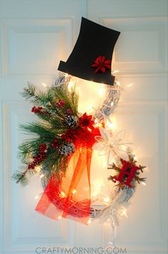Here's an adorable Christmas wreath idea to make this year ~ a lighted grapevine snowman wreath! It is not very hard and looks great during the day and lighted at night! You can personalize it with any colors and monograms. Materials: 2 grapevine wreaths Pine branches White lights White Spray Paint Black Card Stock Tulle …