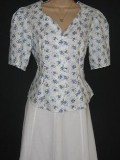 L A U R A A S H L E Y  I dont like ephemeral things, I like things that last forever  A SUMMER WHITE COTTON LAWN BLOUSE, POPULATED IN A PRINT OF BEAUTIFUL PERIWINKLE FLORALS.  IN AN ATTRACTIVE FITTED DESIGN, SEAMED FROM BUST TO HEM, FEATURING AN ELEGANT SCALLOPED NECKLINE AND GATHERED SHORT SLEEVES OF APPROXIMATELY QUARTER LENGTH. THE BLOUSE FASTENS WITH FIVE SELF-COVERED ROULEAU-LOOP BUTTONS. THIS VERSATILE SEPARATE IS SUITABLE FOR FORMAL OR ELEGANT CASUAL WEAR AND WILL BE A MOST USEFUL…