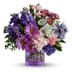 Love is a many splendored thing indeed when it is expressed with this dramatic array of fresh flowers in a stylish lavender cube vase. She'll be very impressed with this exciting gift – and love you even more.