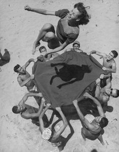 Teenaged boys using blanket to toss their friend, Norma Baker, into the air on the beach, California, 1948.