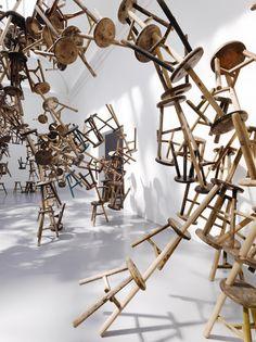 Het is een foto van stoelen die bewegen, denk je.. De stoelen zitten vast, alleen door de manier waarop ze staan/zweven lijken ze door de kamer gesmeten te worden.