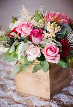 pinkes Blumenarragement in einer Holzkiste