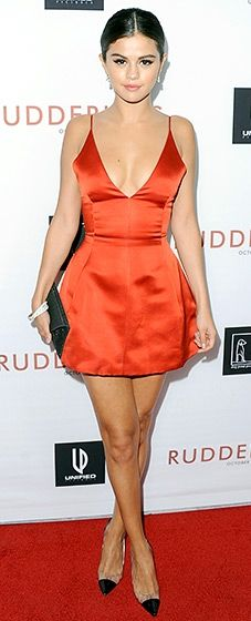 Selena Gomez sizzled in a red-hot Dior dress, transparent Manolo Blahnik heels, and a VBH envelope clutch.