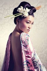 pastel colours and the dramatic effect of the chopsticks positioned in the hair with the oriental flowers