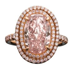 A Natural Fancy Pink diamond captivates the eye in this dazzling ring. This 4.21-carat oval-cut gem, exhibits a wondrous rosy hue with flashes of rich honey brown. Set amongst two rows of full-cut natural pink diamonds, weighing .71 total carats, that flow down the 18K yellow and rose gold shank