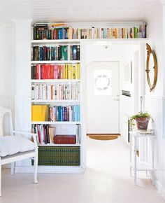 Bookcase above the door. Utilize every inch of space. Don't have clutter, but organization. Living in a small space is doable. We don't need huge homes. Image via Apartment Therapy