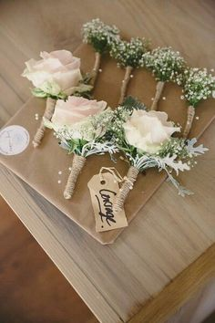 Rose, gypsophilia, dusty miller buttonholes with twine trim