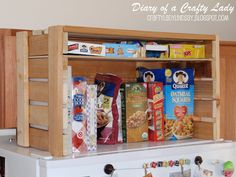 wooden crate storage for over the fridge, w/ a cloth door. Great idea!