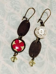 Opposites Attract earring, featuring Dark Chocolate patinated brass, preserved flower, button, and Swarovski crystals. by GemJelly on Etsy