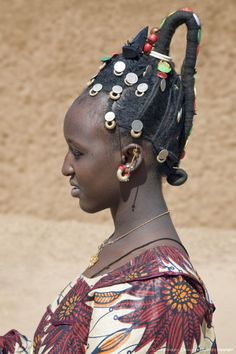 Mali, Gao. A Songhay woman at Gao market with an elaborate coiffure typical of her tribe. The silver coins are old French francs and British West Africa coins dating back one hundred years.