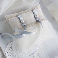 """四隅に輝くラインストーンとチュールをあしらった""""I DO""""シリーズから、サムシングブルーのリングピローが登場です。ウェディングドレスの雰囲気を邪魔することのないクラッシィなデザインは、主張しすぎず、しかしながら存在感はしっかりと。どの式場にもふわりと華を添えることでしょう。アイボリーのシャンタン生地のピローとオフホワイトのチュールを基本に、ポイントにはスモーキーアイボリーのグログランリボンに重ねた2種類のシルバーのレース。アクセントにはシルバーレースに載せたパール&ラインストーンと、ペールブルーのサテンリボンをコットンパールで留めて。何度も色合わせと素材合わせを重ねて、しっくりと溶け込むような組み合わせに辿りつきました。レースとリボンは国内外の有名ブランドでも使われているメーカーのものを、ラインストーンとパール(コットンパールは除く)は全てスワロフスキー社のものを使用しております。◆◆◆大切な指輪は、4枚目の画像のようにコットンパールとサテンリボンの上部分に引っ掛けてお載せしていただけたらと存じます。◆◆お箱に入れてギフトラッピングをしてお送りします◆..."""