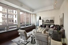 This NYC living room has wood flooring, a window bench, gray sectional couch, patterned coffee table, black floor lamp and horse photography.