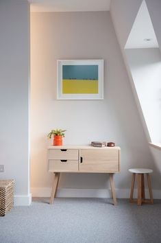 Colourful accents, including orange lamps and brightly coloured artwork, offset the simple finishes of white-painted walls and light grey carpeting.